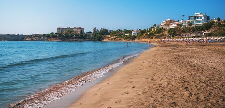Coral Bay beach - popular beach with clear sea water and comfortable sandy beach, many tourists, sunbeds with umbrellas in Peyia village, Cyprus.
