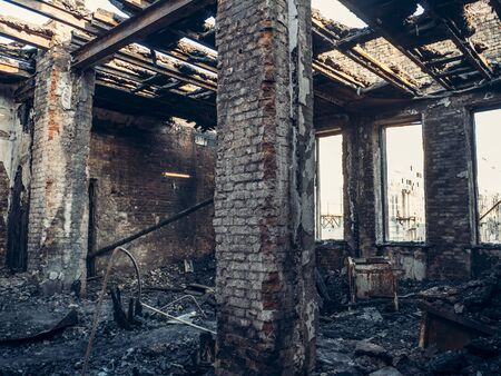 Burnt house interior inside, burned ruined room, remains of furniture in black soot on floor. Fire or war consequences concept.
