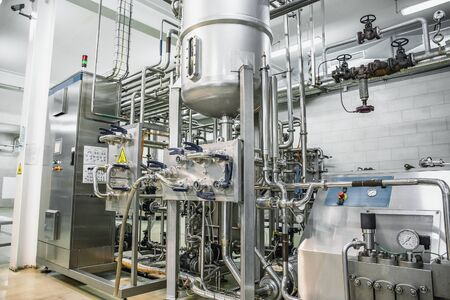 Steel tanks or reservoirs and pipes with system of computerized automated control in food and drink production factory interior.