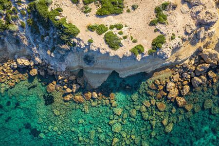 Sea aerial top view, amazing azure water nature background with rock cliff in Cyprus, mediterranean landscape from above.