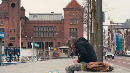 Amsterdam, Netherlands - March 2020 : European homeless man sitting on concrete bench in Amsterdam street, Netherlands.