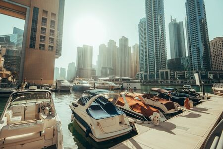 Dubai Marina skyscrapers panorama on background and luxury yacht with boats in water canal, Dubai, United Arab Emirates, toned