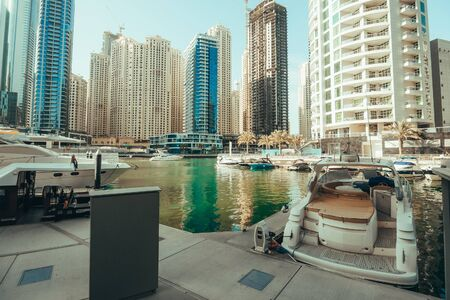 Dubai Marina skyscrapers panorama on background and luxury yacht with boats in water canal, Dubai, United Arab Emirates, toned 스톡 콘텐츠