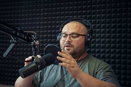 Male radio host talks and broadcasting with microphone in studio.