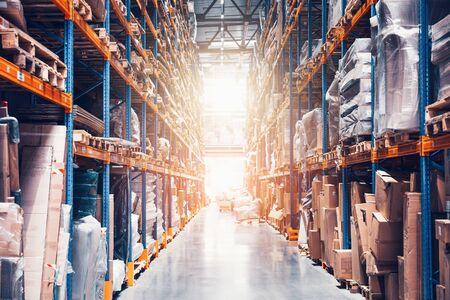 Large distribution warehouse with high shelves, many goods and boxes with abstract light. Imagens