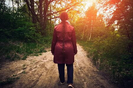 Young woman in red jacket or cloak and braided hair walks in spring forest on footpath, rear view.
