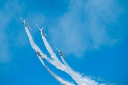 Airplanes with white smoke traces on air show. Pilots make tricks on jets at blue sky background.