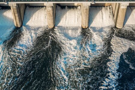 Hydroelectric dam with flowing water through gate, aerial view from drone. Standard-Bild