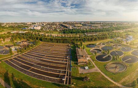 Modern urban wastewater treatment plant with sedimentation tanks and pools for aeration and cleaning of sewer water, aerial view.