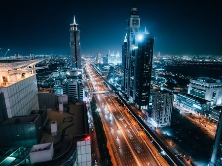 Dubai skyline at night, urban skyscrapers and car traffic, view from above, United Arab Emirates. 스톡 콘텐츠