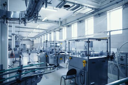 Industrial interior of beverage factory, blue toned. Food and drink production manufacturing.