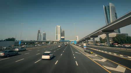Sheikh Zayed Road in Dubai with car traffic in sunny day, United Arab Emirates.