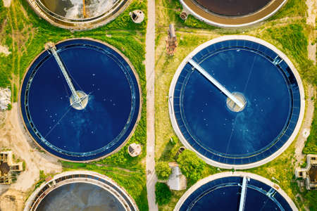 Wastewater treatment plant, round pools for filtration of dirty or sewage water, aerial top view. Banco de Imagens
