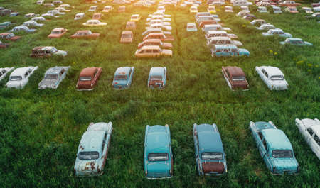 Aerial view of rows of old abandoned rusty vehicles, forgotten retro cars on green grass meadow. 版權商用圖片