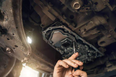 CVT gearbox close up, worker hands changing oil and making maintenance in new modern variator automatic transmission on SUV in Car Service.