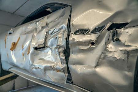 Broken or damaged sport car after road accident or crash in garage repair service shop, close up.