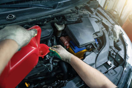 Pouring new engine oil from canister into motor funnel at car service, close up.
