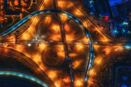 Large roundabout or road transport junction at night with car traffic, aerial top view.