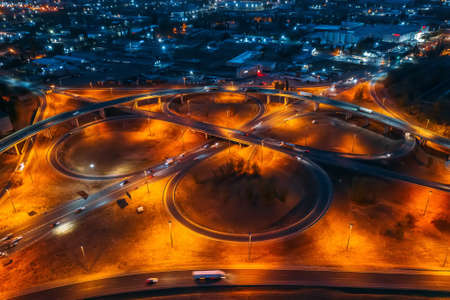 Intersection circle transport junction at night city road with car traffic, aerial view from drone.