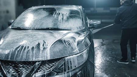 Car washing at night. Man cleaning his car using high pressure water at self-service. 版權商用圖片