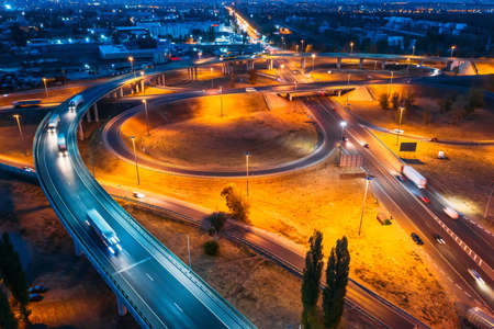 Intersection transport junction at night city road with bridges and car traffic, aerial view.