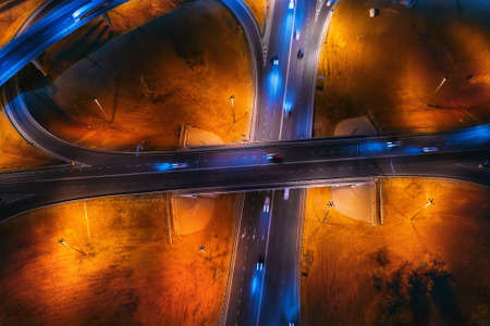 Road intersection with bridges and highways, car traffic and trucks in blurred speed motion, aerial top view at night.