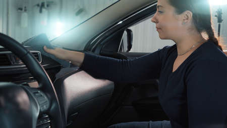 Woman cleaning microfiber flyer plastic panel of car inside, dry cleaning and disinfection of car.