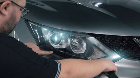 Worker pastes over headlamp optics with special tape around perimeter, prepares for polishing. 版權商用圖片