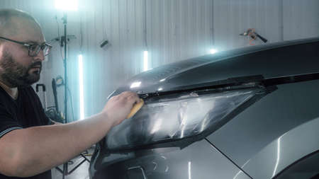 Car detailing. Polisher applies special polishing compound or paste or wax to optics of car headlight with sponge, close up.