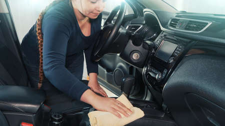Professional woman car washer cleaning and disinfecting car interior with microfiber towel. Car detailing concept. 版權商用圖片