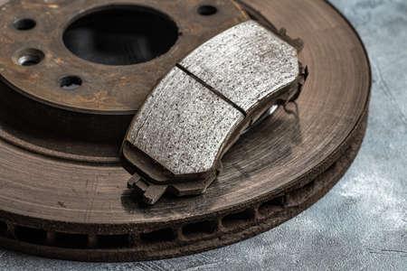 Old worn out car brake disc and brake pads, macro shot close-up.