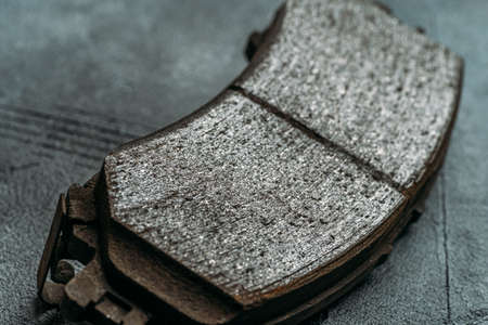Used worn out car brake pads need to change, close up.