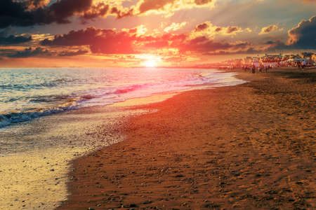 Twilight sea sunset landscape. Mediterranean sand beach of Italian Lido di Ostia in evening with beautiful sun near water horizon.