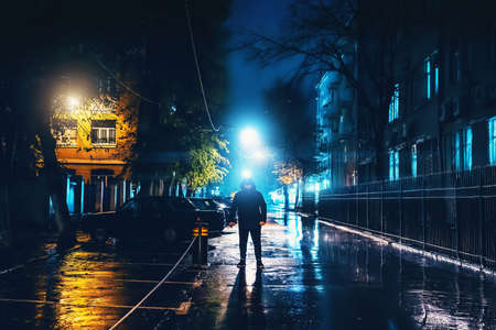Silhouette of alone stranger in hood at night city street in rain. Creepy killer or stalker, criminal stands in shadow with urban lights reflected in puddles. Thriller horror mysterious atmosphere.