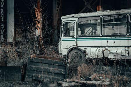 Old rusty broken abandoned bus in dark industrial post apocalyptic landscape.
