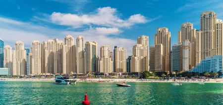 Panorama of Dubai Marina, view from sea on sandy beach and modern buildings on coastline, UAE.
