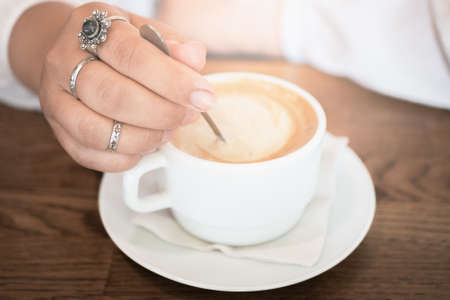 Coffee late in white cup and female hand with spoon, close up. Good morning concept idea. Reklamní fotografie