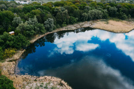 Aerial view of lake with reflection of blue sky with clouds, spring and travel nature landscape.
