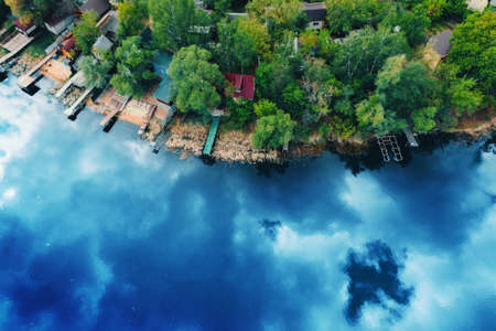 Lake or river with reflected blue spring cloud sky and green forest coastline with small houses and water piers for boats, aerial top view from drone beautiful nature landscape, copy space