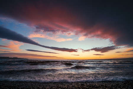 Dramatic bright colorful sunset above tropical sea waves.