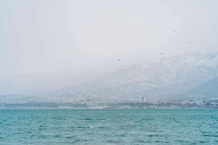 Gelendzhik city in winter in snowy weather, mountains covered with snow, waves and wind on sea bay water surface, no people walking in city. Reklamní fotografie