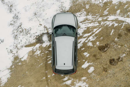 Aerial top view of modern off road SUV car on ground covered with snow, winter travel adventure concept.