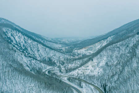 Aerial view from drone above mountain gorge between mountain peaks in winter time in snowy weather.