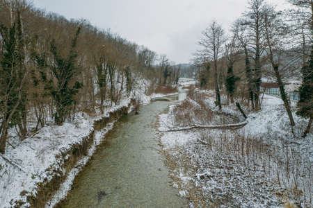 Aerial view of riverbed in mountain gorge. Winter river in snow weather. Reklamní fotografie