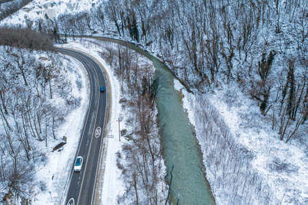 Aerial view of road and river in mountain gorge in snowy day, winter travel and car journey exploration concept.