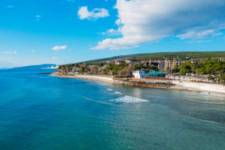 Aerial view of Divnomorskoe small sea resort town on Black Sea coast, beautiful seascape in sunny day.