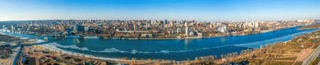 Panoramic view of Don river and right bank of Rostov-on-Don city with many buildings, Russian big city in winter time aerial view.