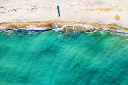 Aerial top view of single human figure casting shadow on sandy beach, standing by sea with beautiful azure tropical sea water and waves, copy space for your text.