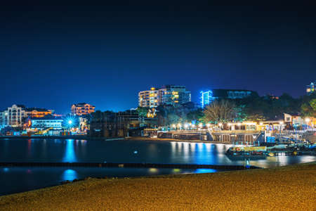 Gelendzhik sea resort beach coastline at night with illuminated modern buildings at background reflected in sea surface .