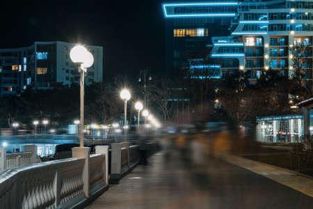 People in blurred motion on illuminated night city street.